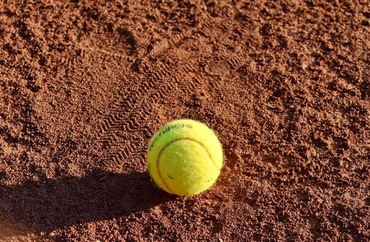 Tennis ball sitting on dirt