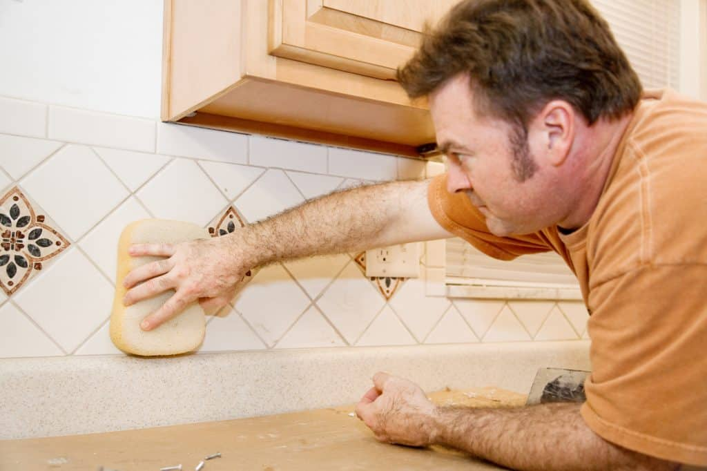 A tiler using a sponge for grouting and wiping water over tiles