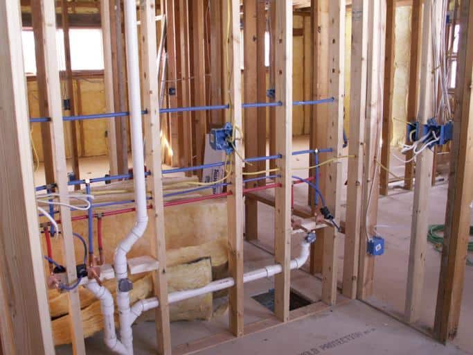 Can you run plumbing and electrics through the same hole?