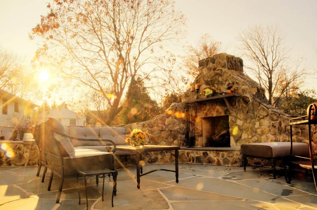 Sunlit patio with stone fireplace and trees in the background