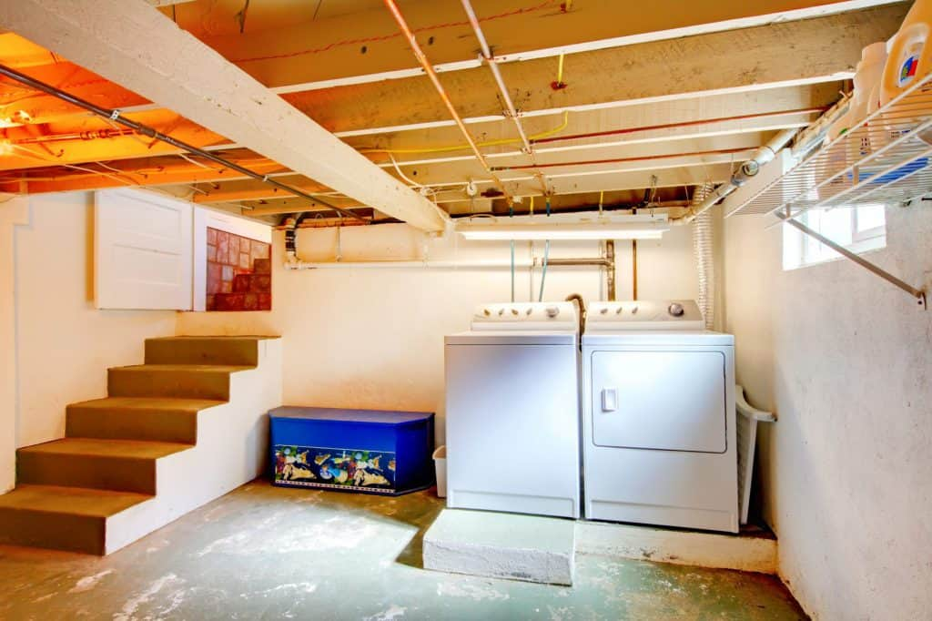 A basement with various exposed wires and pipes