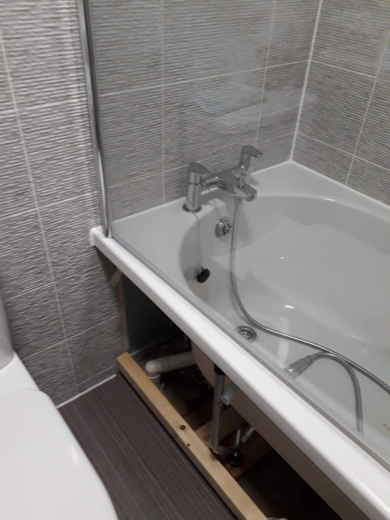 A bath with side panel removed and tiles around it