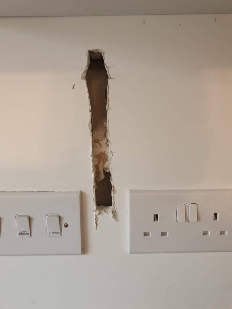 A hole in drywall before tiling it dot and dab adhesive can be seen behind drywall
