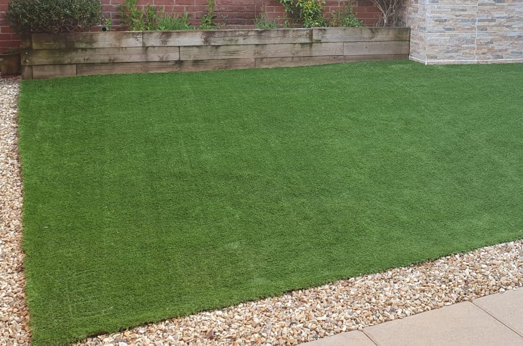 Artificial fake grass with some dirt on it which could be vacuumed up