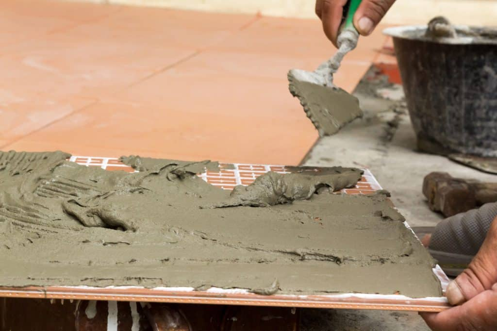 Tile adhesive spread onto the back of a tile