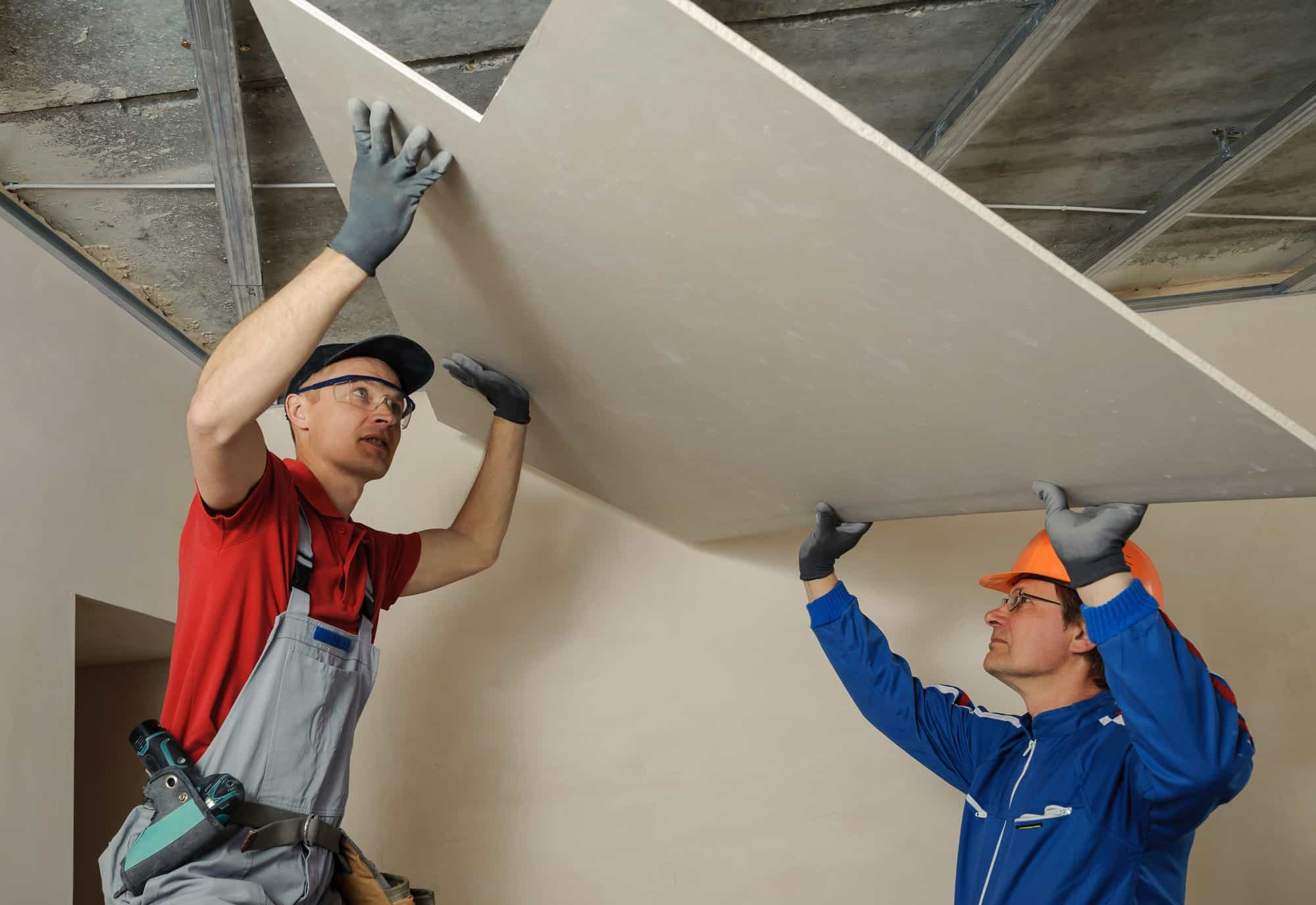 Installers moving drywall into position on a ceiling