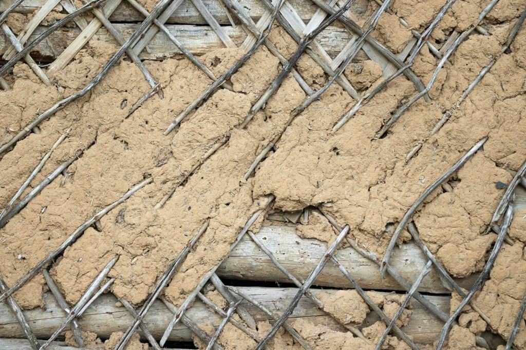 The old wall is covered with lath and covered with clay