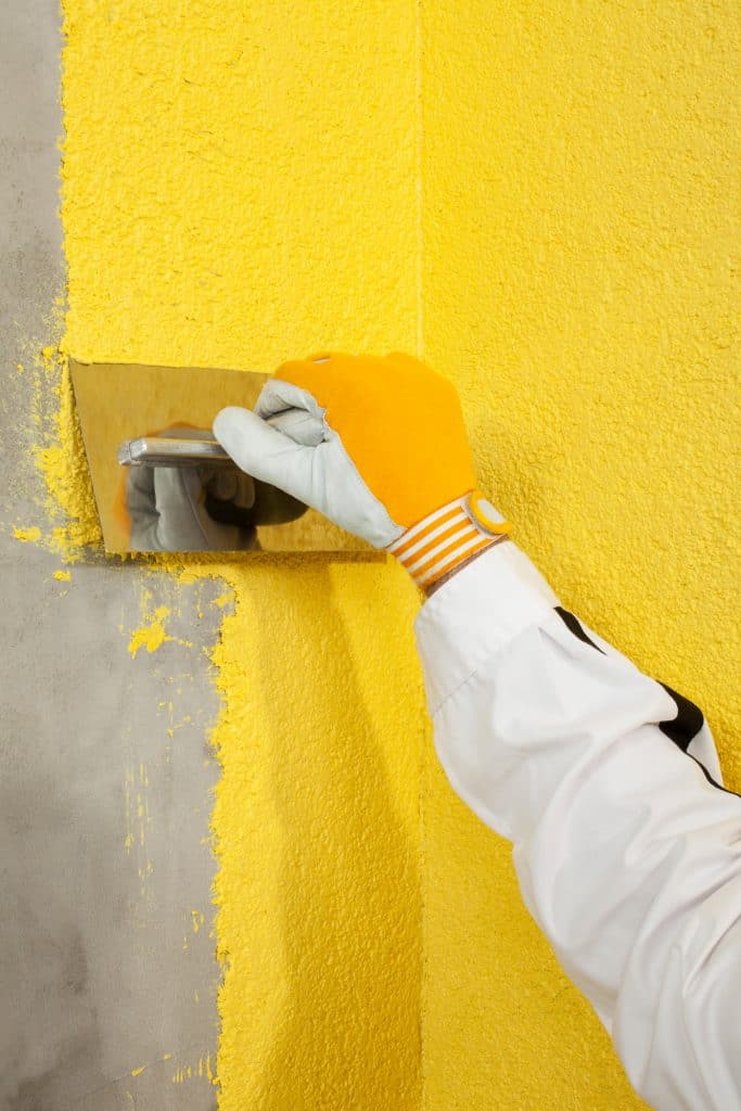 Using a trowel to spread color plaster onto the corner of a wall