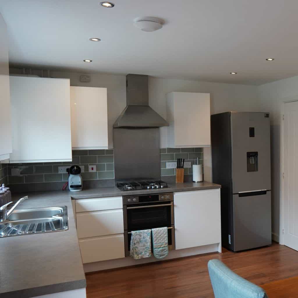 A kitchen with a cooker extraction hood and ceiling exhaust fan
