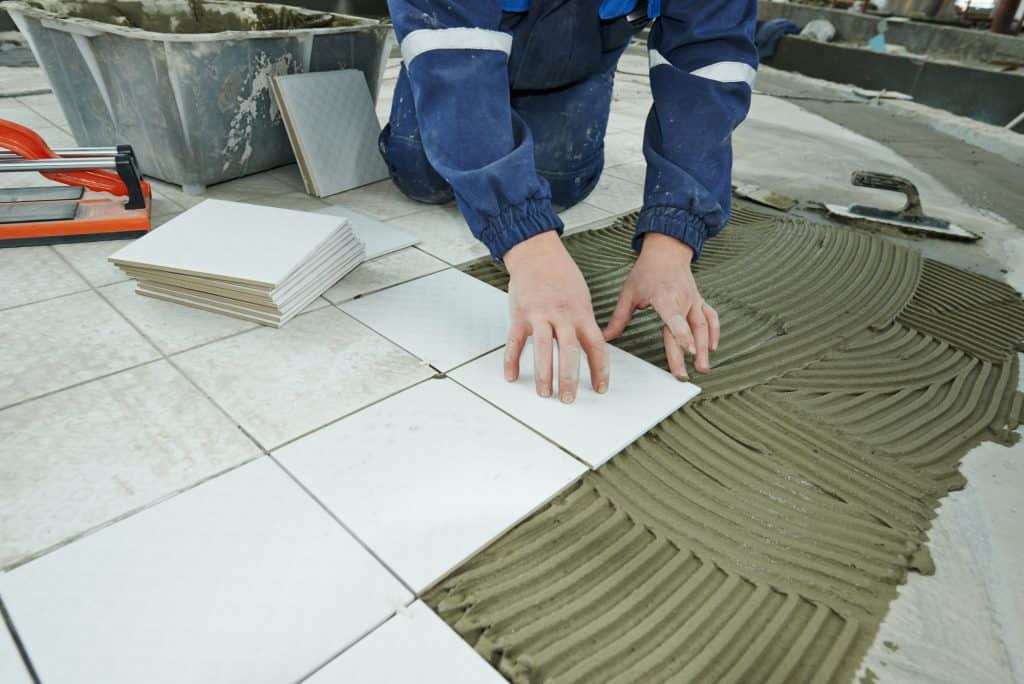 A contractor laying tile and adhesive directly onto a concrete subfloor