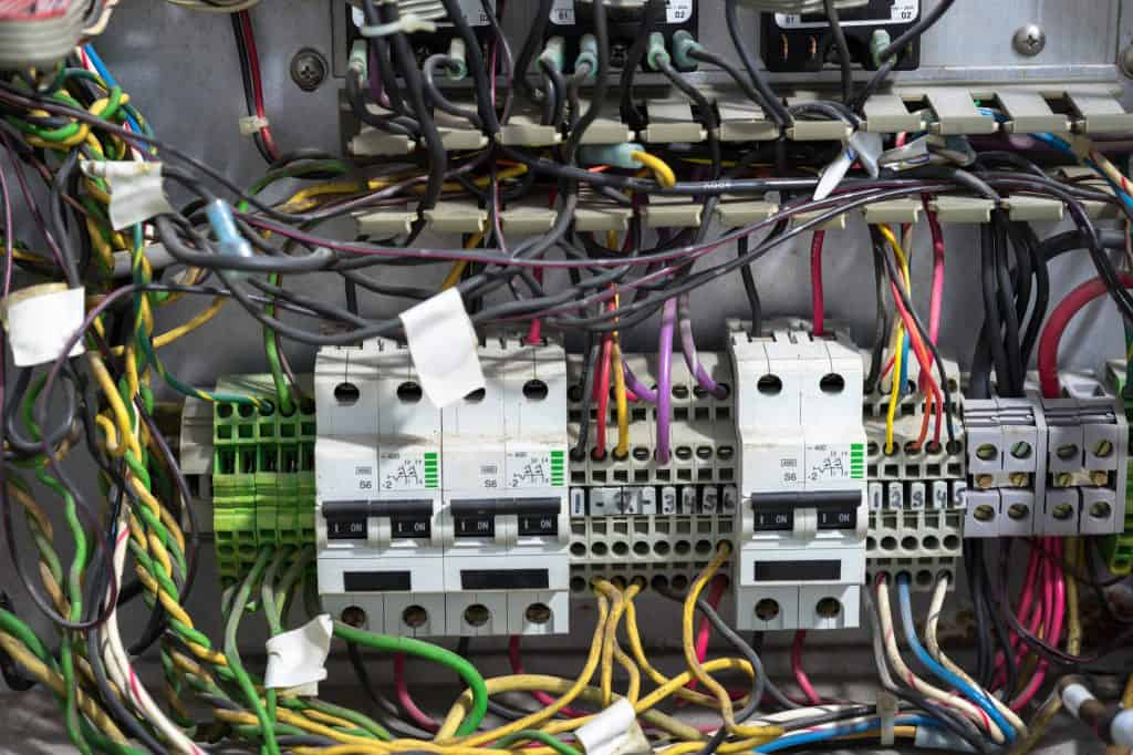 An old messy breaker panel with various connected wires
